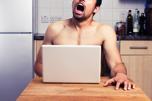 A naked man watching pornography in his kitchen